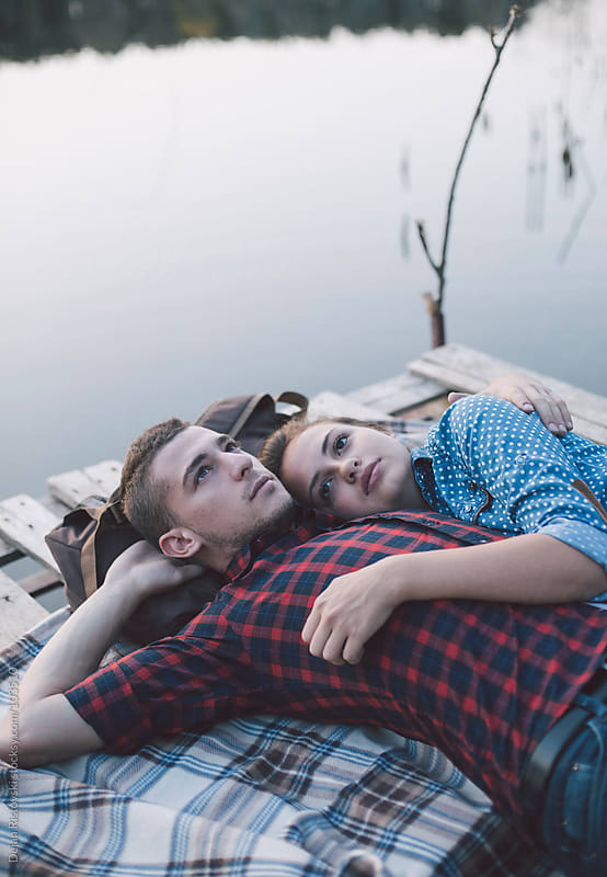 Couple lying by the lake by Dejan Ristovski for Stocksy United