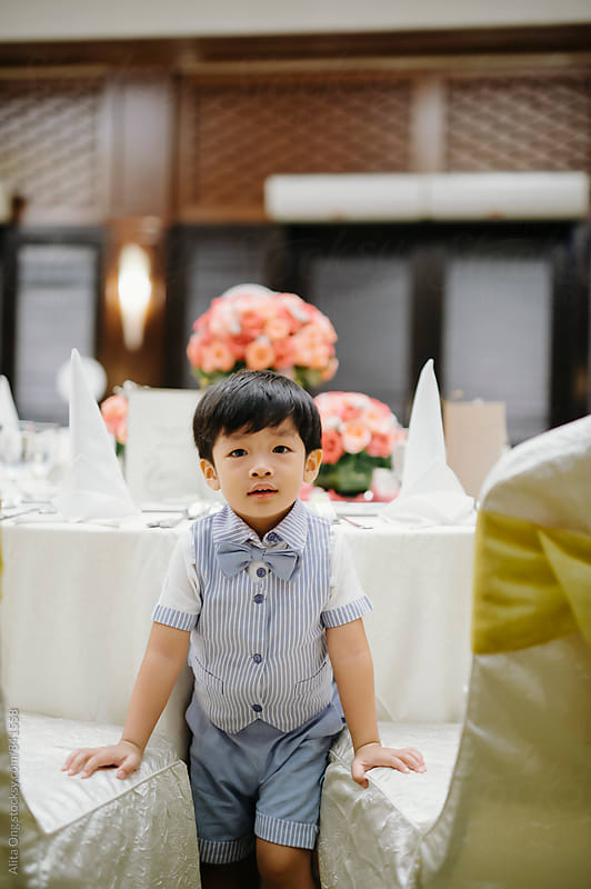 Kid at formal dinner by Alita Ong for Stocksy United