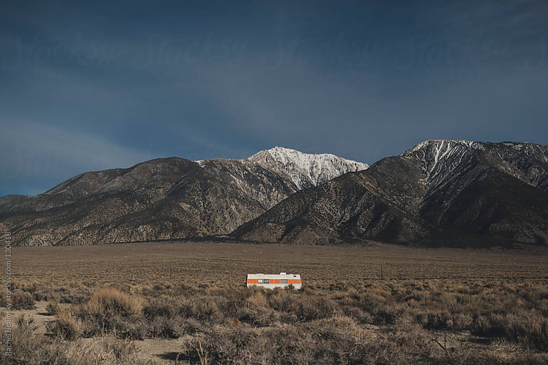 Majestic snow-capped desert mountains behind a lone trailer  by Rachel Bellinsky for Stocksy United