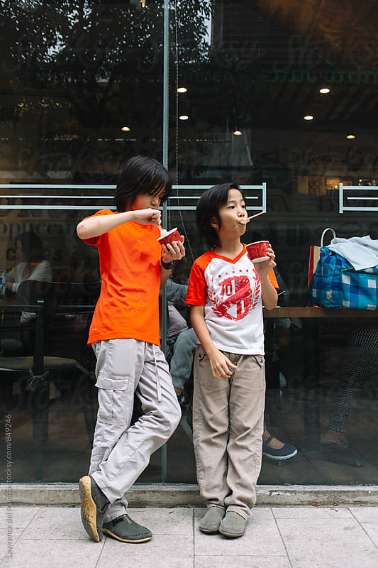 Two brothers enjoying their ice cream dessert outside of a store in a mall by Lawrence del Mundo for Stocksy United