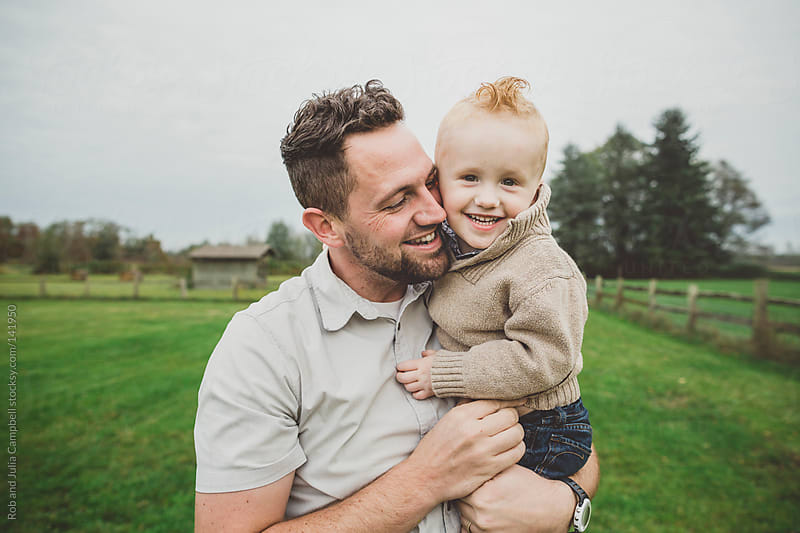 Playful father enjoying young son in farm field by Rob and Julia Campbell for Stocksy United