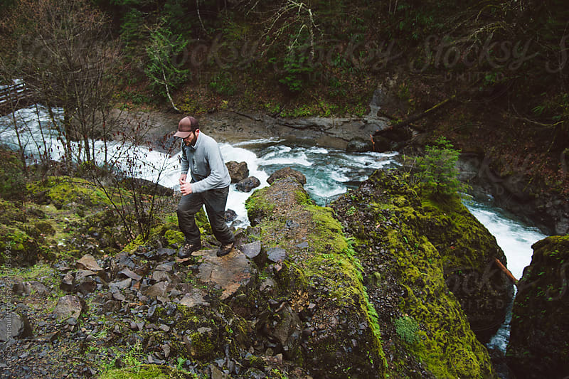 Man climbing up big mossy rocks by riverbed. by Kate Daigneault for Stocksy United
