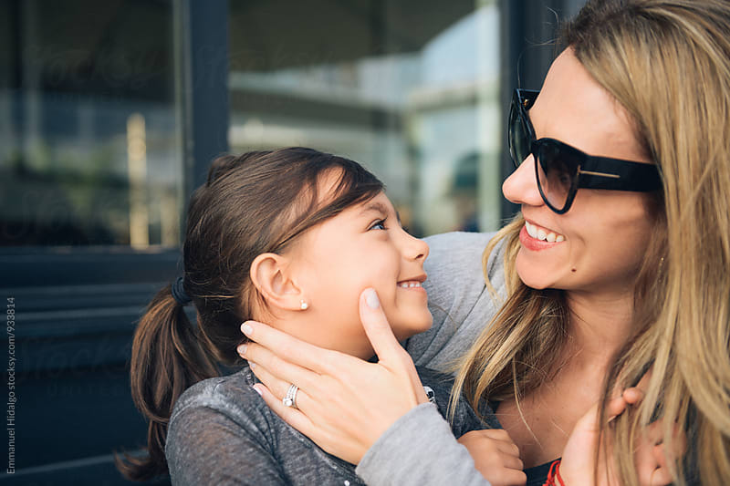 Mother and daughter looking and smiling at each other by Emmanuel Hidalgo for Stocksy United