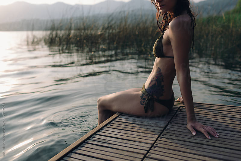 Attractive woman enjoying the tranquility of the lake at sunset by michela ravasio for Stocksy United