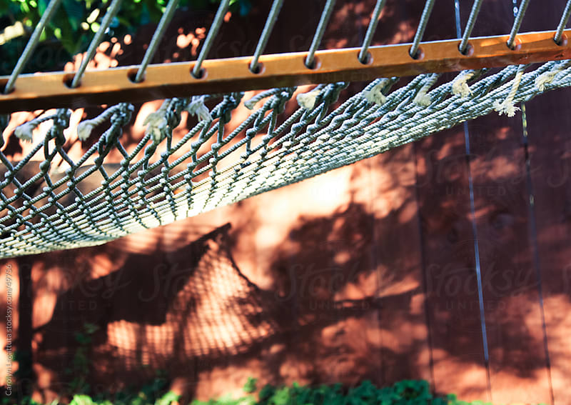 Hammock in the morning light casting a shadow on the fence. by Carolyn Lagattuta for Stocksy United