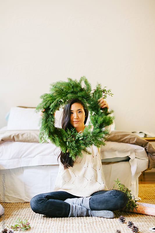Young asian woman holding a Christmas wreath at home. by BONNINSTUDIO for Stocksy United