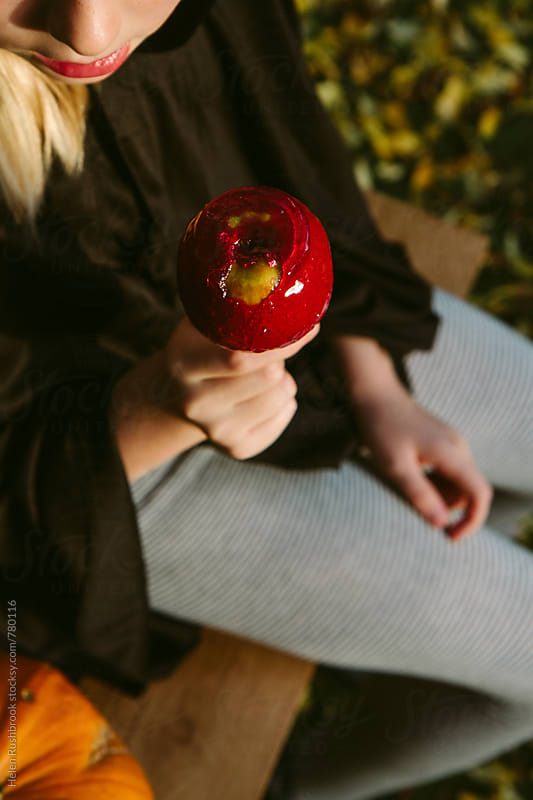 A child holding a toffee apple by Helen Rushbrook for Stocksy United