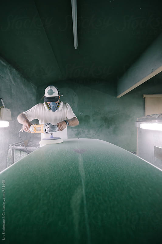 Shaper grinds surface of green surfboard by Urs Siedentop & Co for Stocksy United