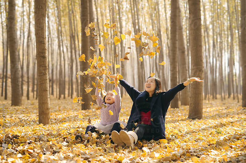 Young mother and daughter playing in autumn wood by MaaHoo Studio for Stocksy United