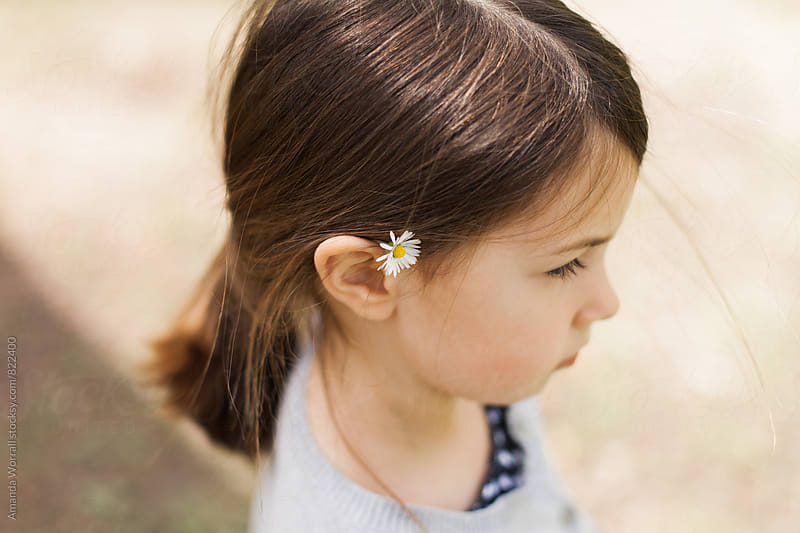 Profile of pretty little girl with small daisy tucked behind her ear by Amanda Worrall for Stocksy United