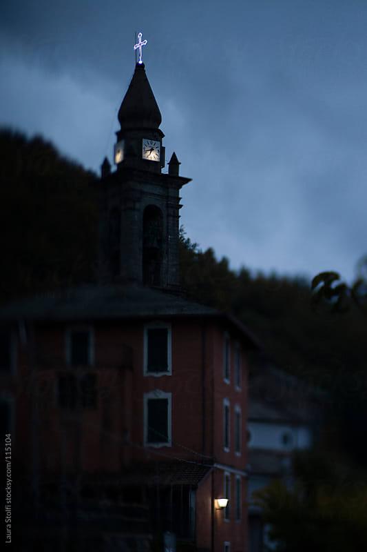 Italian mountain village ancient church's illuminated campanile and clock at dusk by Laura Stolfi for Stocksy United