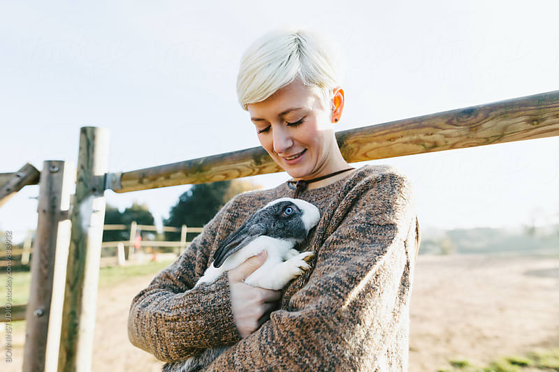 Portrait of a woman holding a cute bunny on farm. by BONNINSTUDIO for Stocksy United