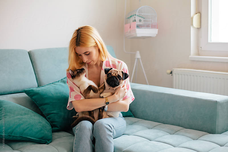 Beautiful blond woman with her pets indoor by Marija Mandic for Stocksy United