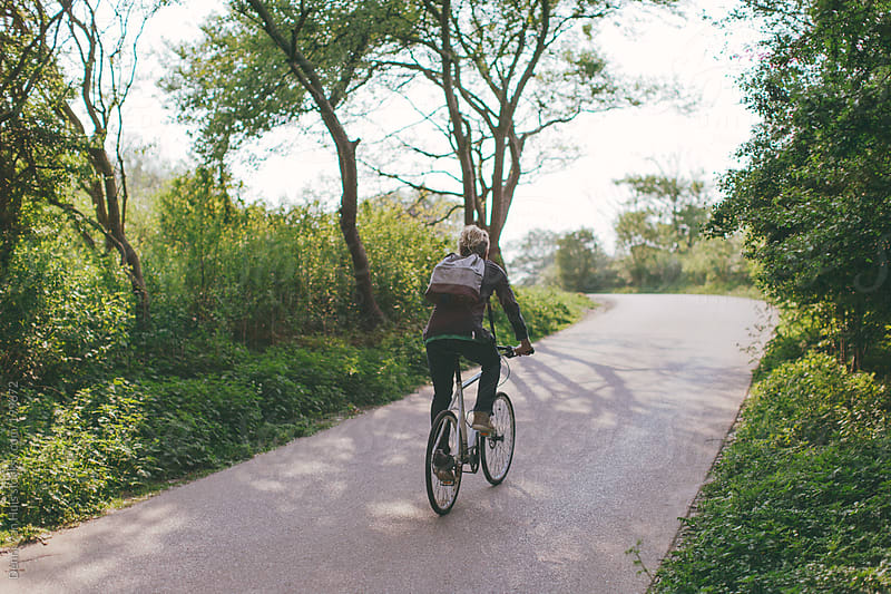 Person riding a bike up a hill. by Denni Van Huis for Stocksy United