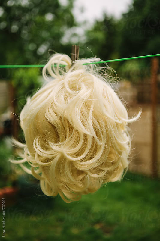 Blonde wig hanging on a washing line to dry by kkgas for Stocksy United