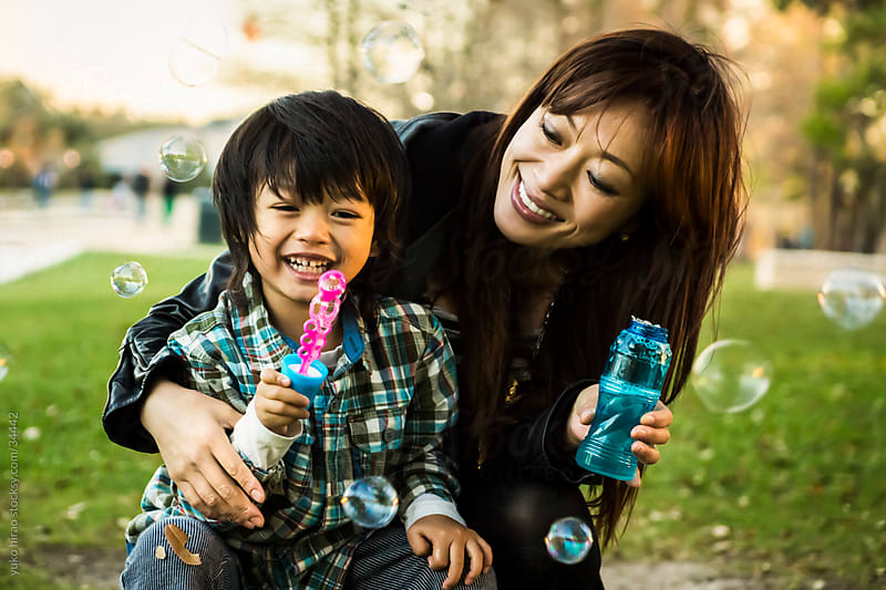Asian mother and son, blowing soap bubbles outdoors by yuko hirao for Stocksy United