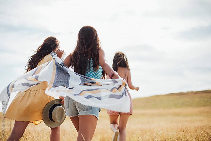 Three Girls Running in a Field by Lumina for Stocksy United