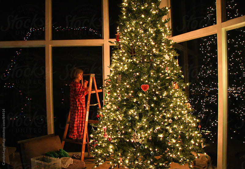Little girl putting ornaments on the Christmas tree by Carolyn Lagattuta for Stocksy United