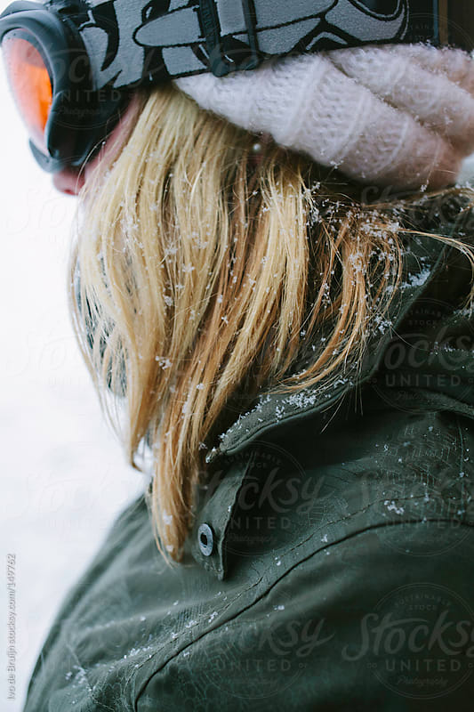 Close up of a blond snowboarder girl with snow in her hair by Ivo de Bruijn for Stocksy United