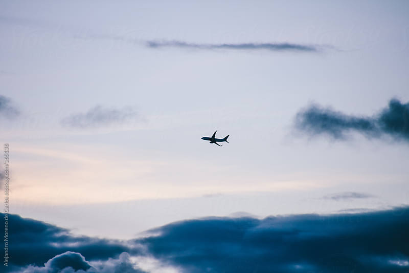 Airplane silhouette on sky with clouds by Alejandro Moreno de Carlos for Stocksy United
