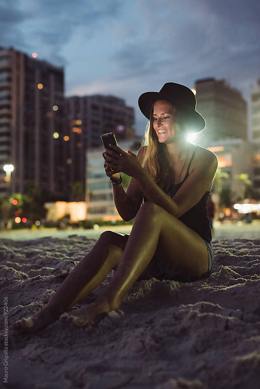 Rio de Janeiro. Brazil. Woman using mobile phone while sitting on the beach at sunset by Mauro Grigollo for Stocksy United