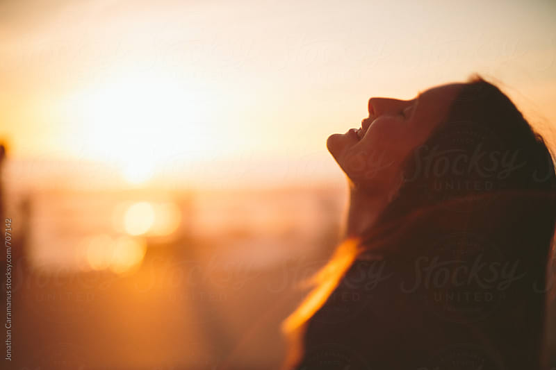 beautiful woman overlooking ocean in golden light of sunrise or sunset with lens flares by Jonathan Caramanus for Stocksy United