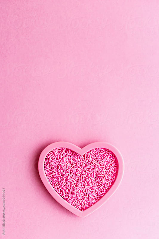 Heart shaped cookie cutter filled with sprinkles by Ruth Black for Stocksy United