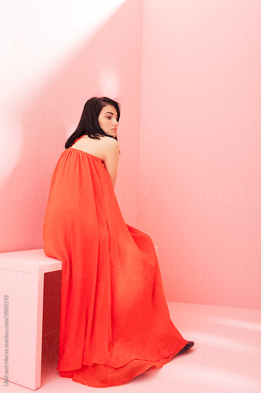 woman with red dress sitting on a pink bench by Ulaş and Merve for Stocksy United