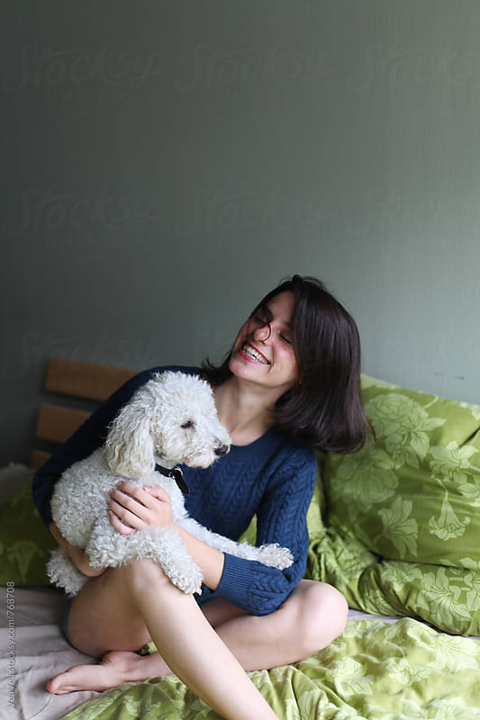 Beautiful happy woman playing with her dog on the bed  by Marija Mandic for Stocksy United
