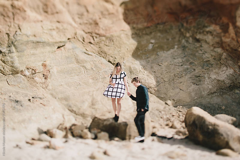 young couple playing on rocks on sunny beach by Nicole Mason for Stocksy United