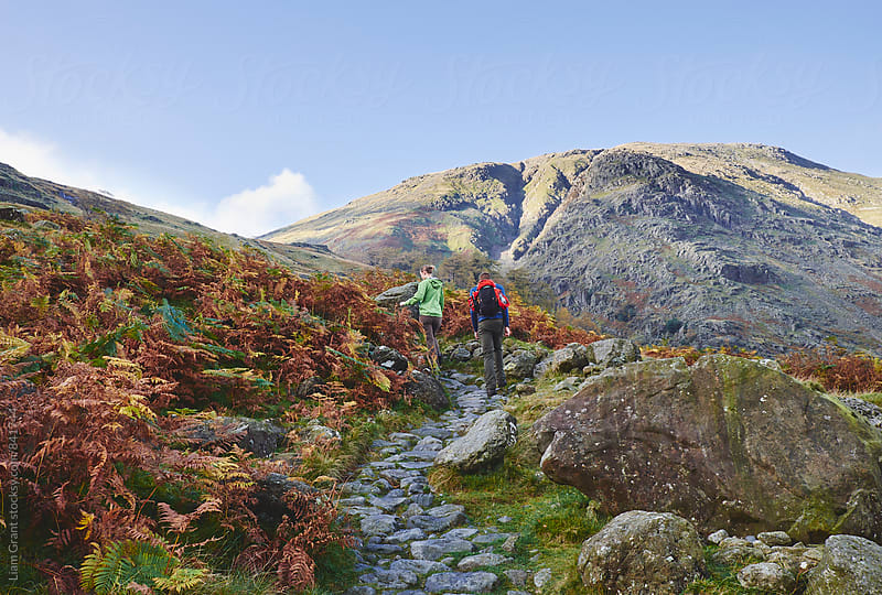 Young couple walking on a mountain path. Cumbria, UK. by Liam Grant for Stocksy United