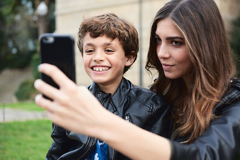 Sister and brother smiling while taking selfie in park by Guille Faingold for Stocksy United