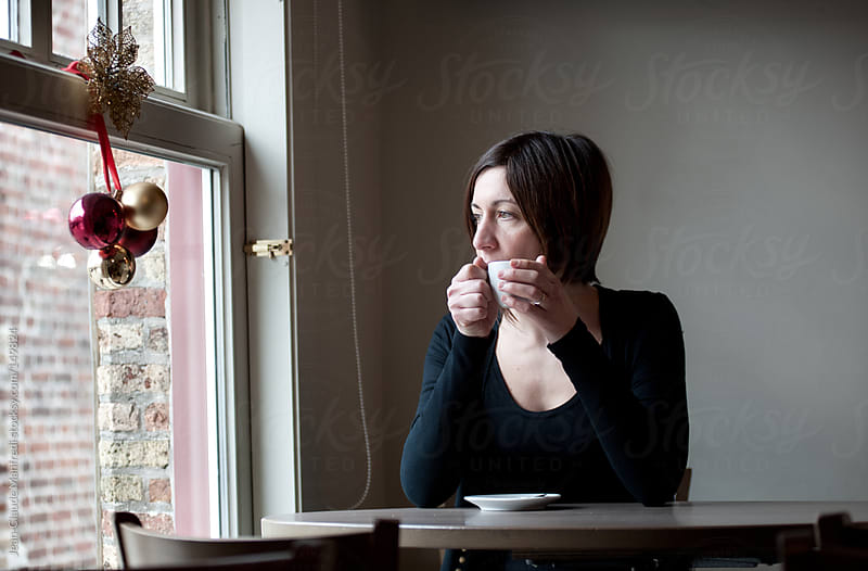 Young woman drinking a cup of coffee looking out the window by Jean-Claude Manfredi for Stocksy United