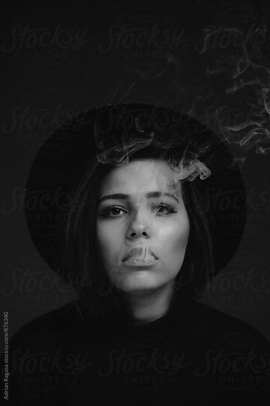 Woman Smoke with Hat by Adrian Ragasa for Stocksy United
