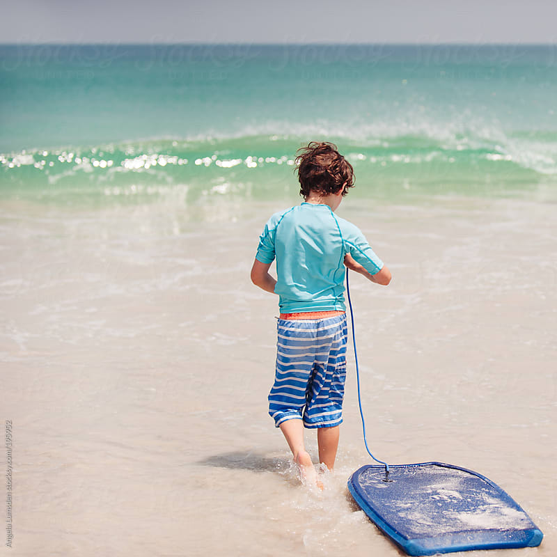 Boy walking into the ocean with his boogie board by Angela Lumsden for Stocksy United