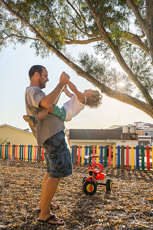 Father playing with his son in the park at sunset by ACALU Studio for Stocksy United
