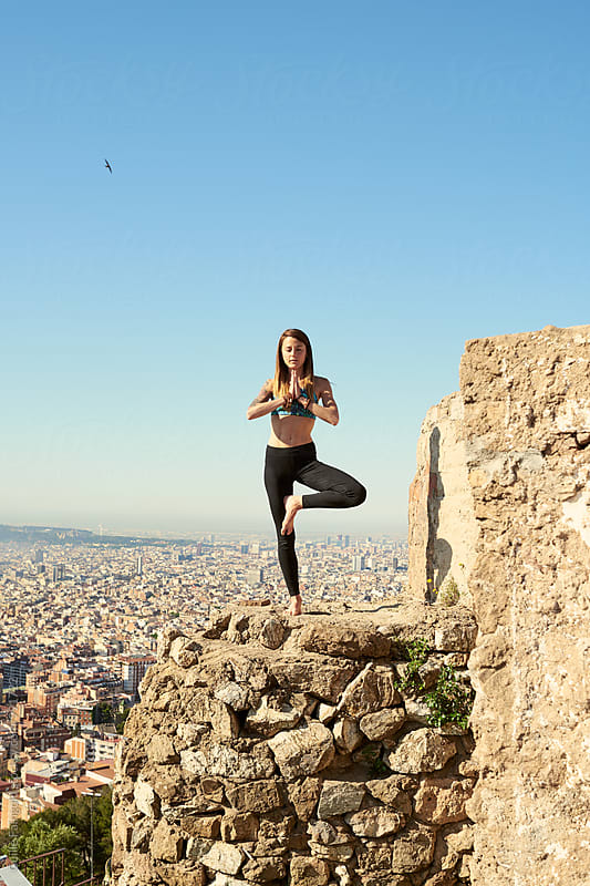 Woman in tree pose with hands in namaste on rocky edge by Guille Faingold for Stocksy United
