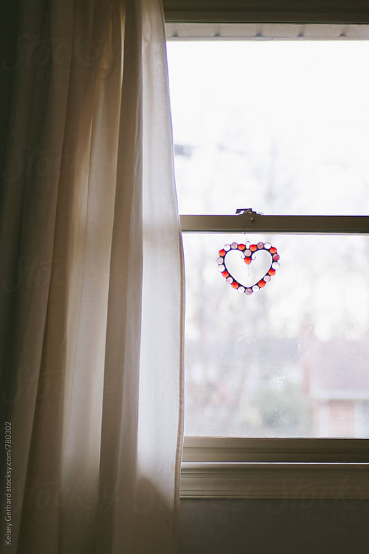 A serene image of a window with a heart ornament. by Kelsey Gerhard for Stocksy United
