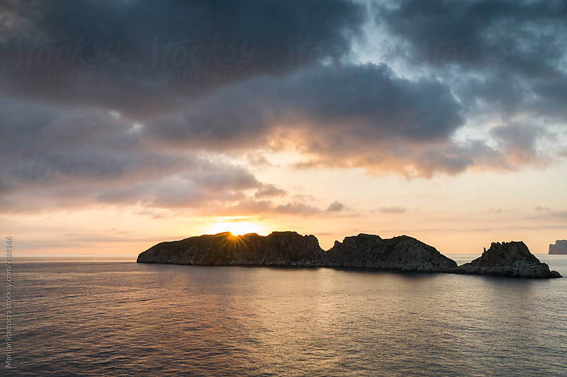 Sun setting behind a small Mediterranean island by Marilar Irastorza for Stocksy United