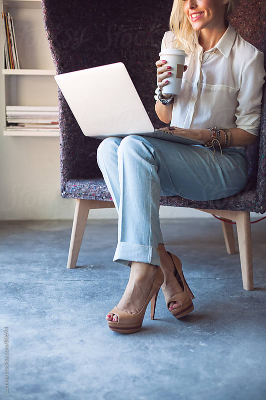 Smiling Businesswoman Drinking Coffee and Working at Her Laptop  by Lumina for Stocksy United
