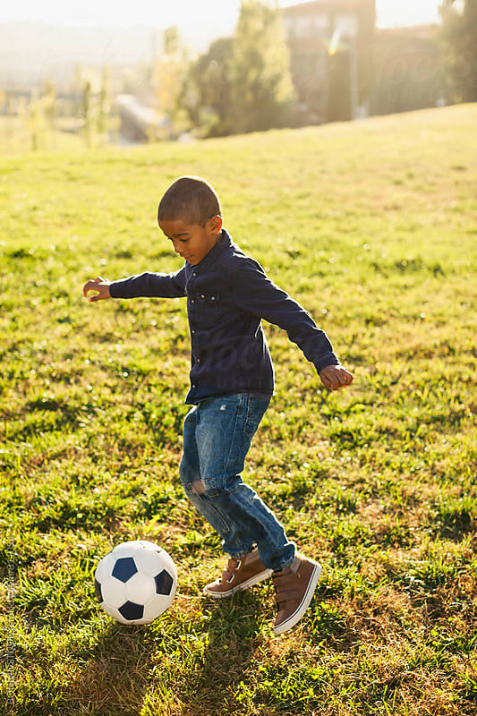 A 5 years old boy playing football in the park. by BONNINSTUDIO for Stocksy United