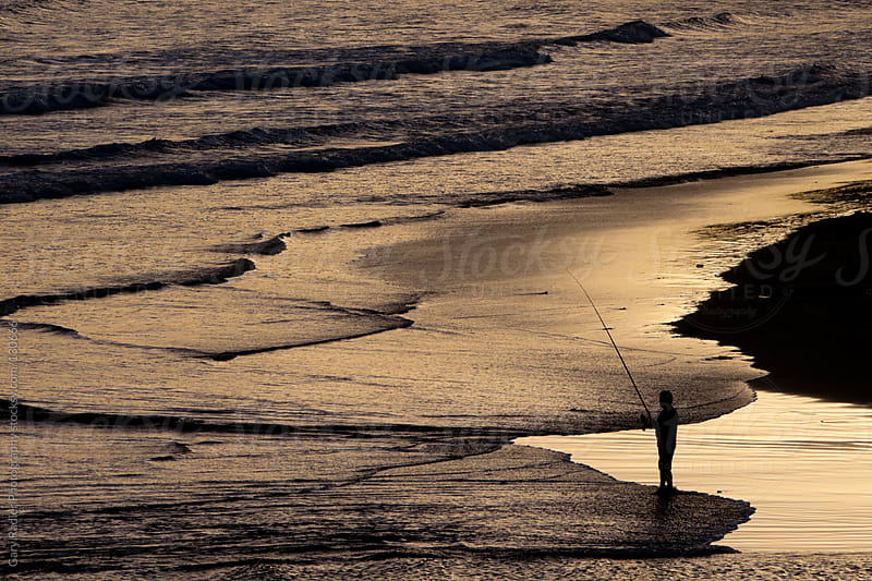Fisherman on a Beach in Silhouette by Gary Radler Photography for Stocksy United