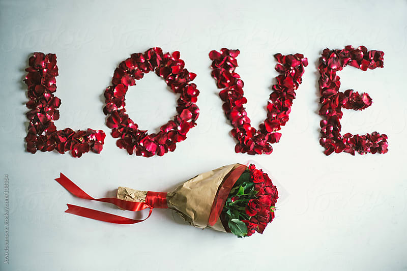 Bouquet of red roses next to a love sign made of rose petals. by Jovo Jovanovic for Stocksy United
