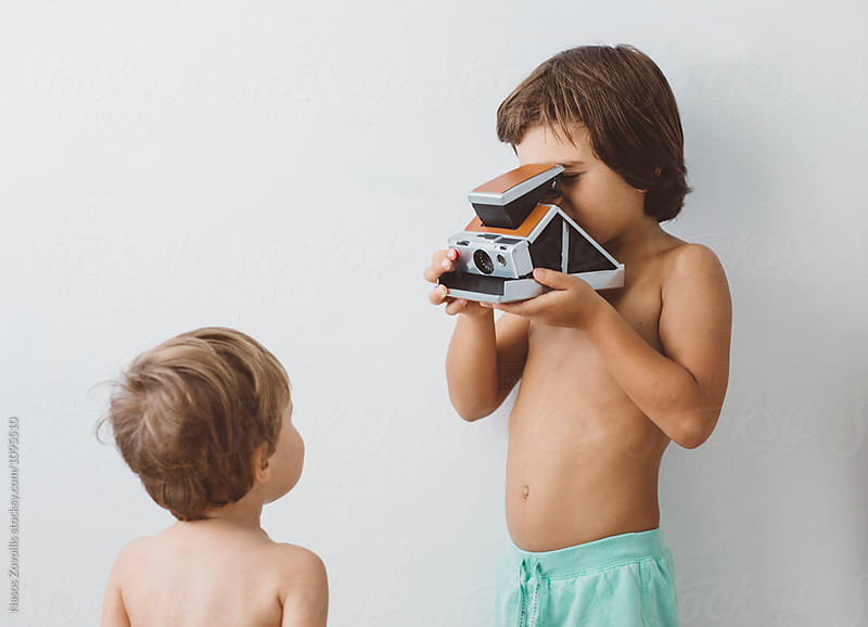 5 year old boy taking photo of his brother with an instant camera by Nasos Zovoilis for Stocksy United