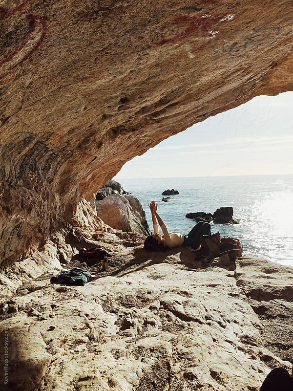 Woman Relaxing in Ocean-side Cave by Kevin Russ for Stocksy United