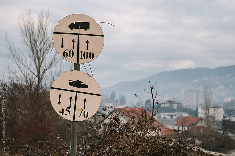 traffic sign - trucks and tanks along the road -in former war zone, kosovo by Leander Nardin for Stocksy United