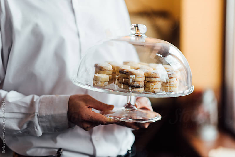 Chef holding a glass container with delicious cakes by Boris Jovanovic for Stocksy United