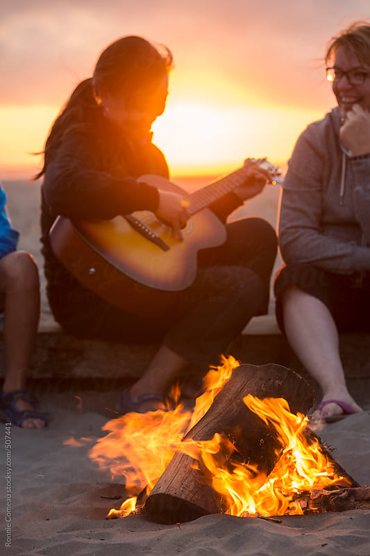 Woman Singing By The Campfire On The Beach by Ronnie Comeau for Stocksy United