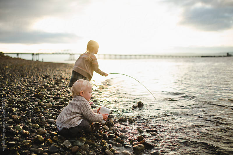 A Toddler boy plays with a fishing buoy while sister fishes in the background by Amanda Voelker for Stocksy United
