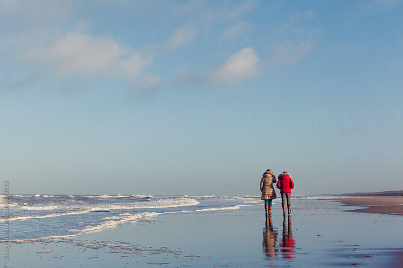 Two older ladies taking a long walk on the beach by Cindy Prins for Stocksy United